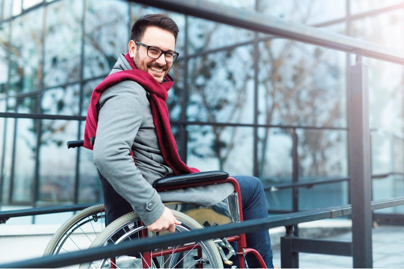 Jeune homme en fauteuil roulant qui sourit